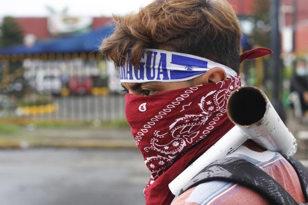 Naamioitunut mielenosoittaja yliopiston ulkopuolella Managuassa Nicaraguassa 23. toukokuuta.