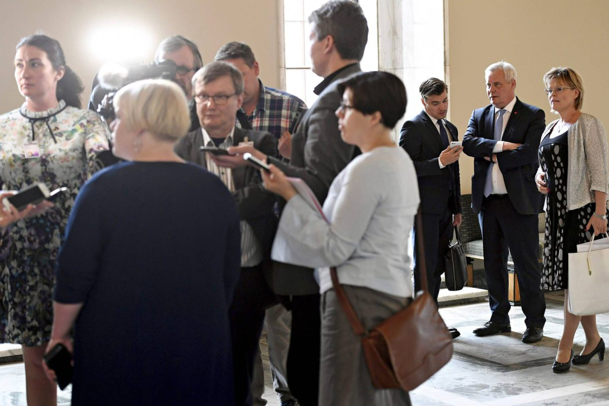 Antti Rinne (sd) ja Sari Tanus (kd) kuuntelivat taustalla kun ministeri Annika Saarikko (kesk) vastaili toimittajien sotekysymyksiin eduskunnassa.