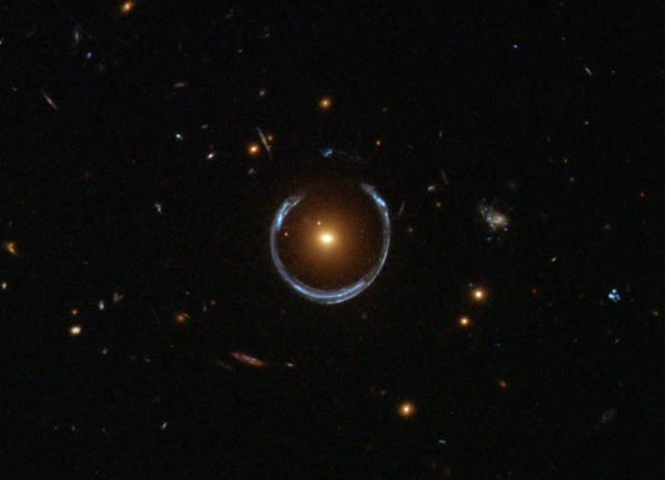 Hubblen gravitaatiolinssistä ottamassa kuvassa näkyy, kuinka lähempänä oleva galaksi taivuttaa kauempana olevan valoa.