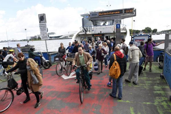 Ihmisiä nousemassa lautan kyydistä Alankomaiden pääkaupungissa Amsterdamissa.