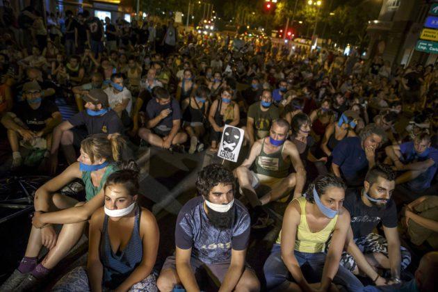 """Mielenosoittajat protestoivat Espanjan """"suukapulalakia"""" parlamentin edustalla Madridissa heinäkuussa 2015."""