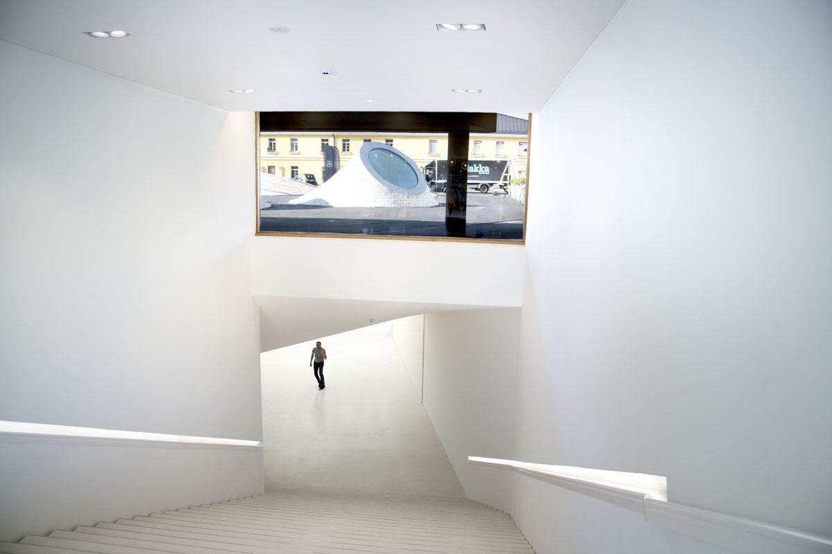Portaat johdattavat museon aulaan, näyttelytilaan sekä taidetyöpajoihin. Ikkunan läpi näkyy Lasipalatsin aukio sekä kolme historiallista kerrostumaa, 1800-luvun kasarmi, 1900-luvun lasipalatsia ja uuden vuosituhannen Amos Rex.