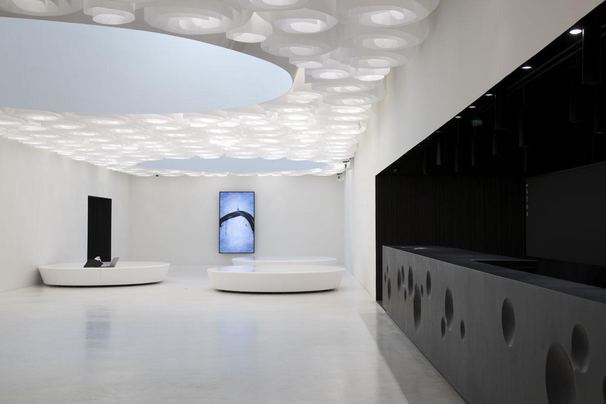 """Museon pääaula on pelkistetty, valkoinen tila, jossa voi """"puhdistautua"""" ennen näyttelytilaan astumista. Doctor Designin suunnittelema jättimäinen valokatto toistaa pilvien liikkeitä. Taustalla TeamLabin tilallinen kalligrafiateos Enso."""