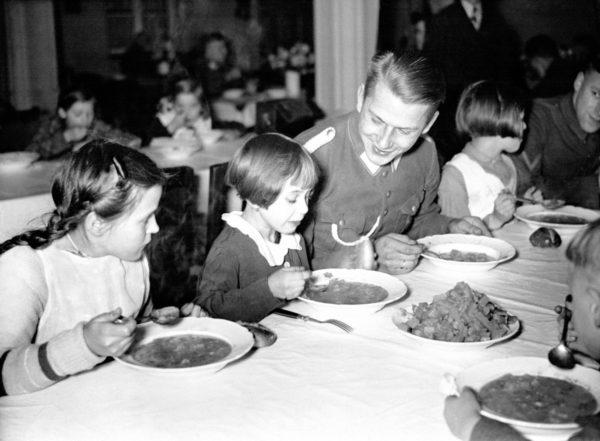 Berliiniläislapset lounastivat yhdessä Hitler-Jugendin edustajan kanssa 6. marraskuuta 1935.