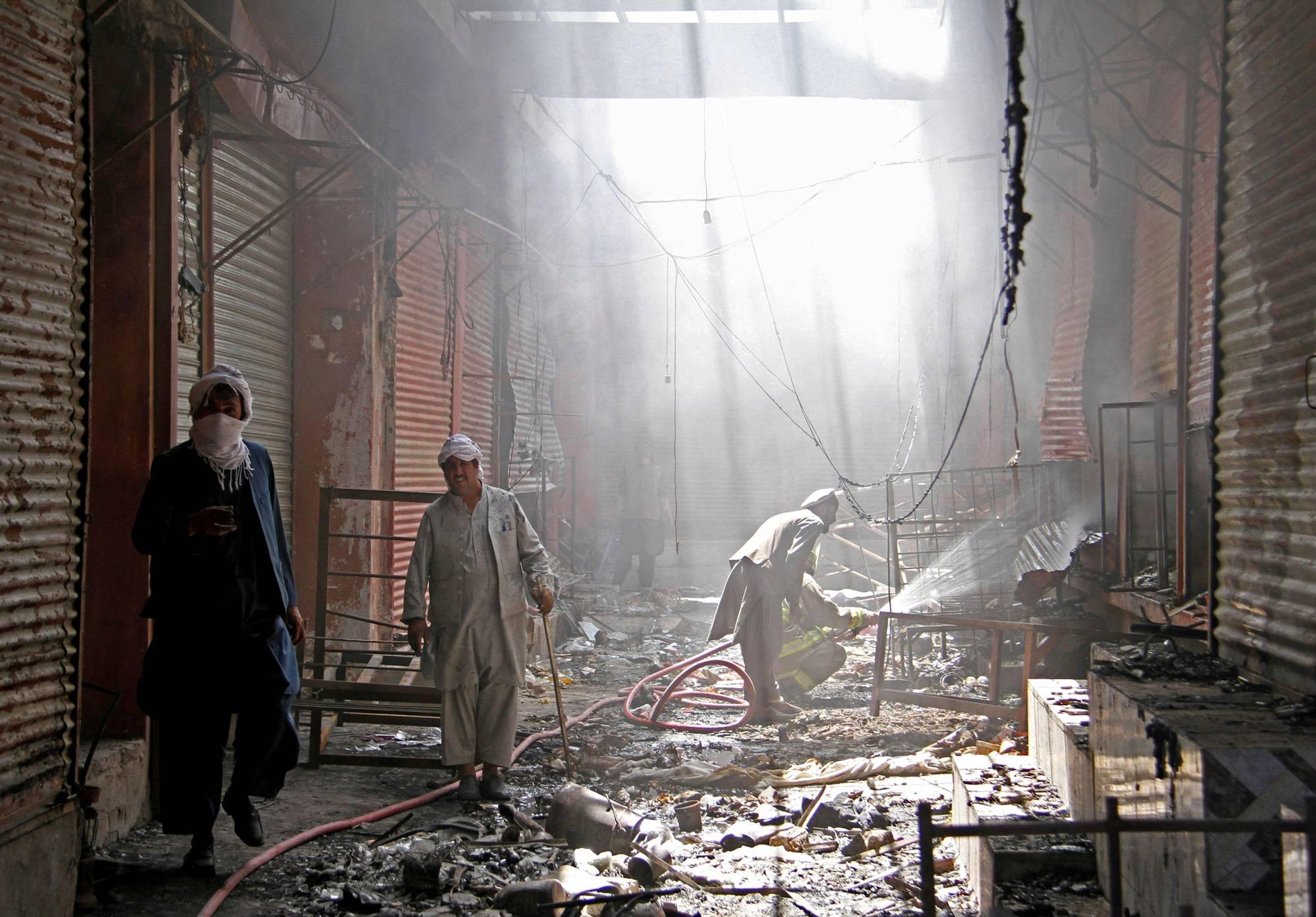 Palomiehet siivoavat talebanin hyökkäyksen jälkiä Ghaznissa 14. elokuuta.