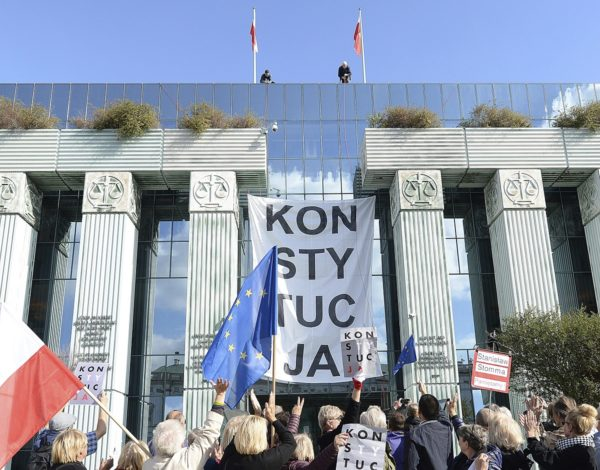 "XCS150; FILE - In this Oct. 8, 2018 file photo, government opponents with signs reading ""Constitution"" protest an overhaul of the justice system and the forced early retirement of Supreme Court judges aged 65 and above, before the court's building in Warsaw, Poland. The European Union's top court ruled on Friday, October 19, 2018, that Poland must immediately suspend the politically-charged forcing out of judges.(AP Photo) AP / LEHTIKUVA / CZAREK SOKOLOWSKI"