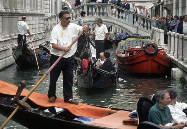 Gondolieerit kuljettavat asiakkaita kapeassa kanavassa Venetsiassa.