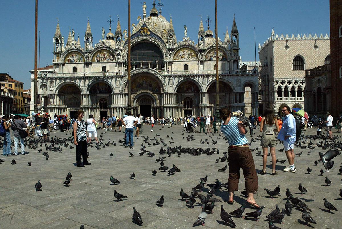 Puluja ja ihmisiä Basilica di San Marcon edessä Venetsiassa.