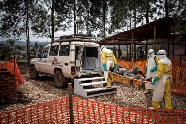 Lääkärit ilman rajoja -järjestön tunnuksin merkitty maastoauto kuljettaa potilasta.
