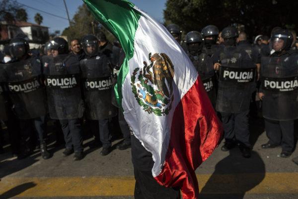 Siirtolaisia vastustava mielenosoittaja ja poliiseja Tijuanassa 18. marraskuuta 2018.