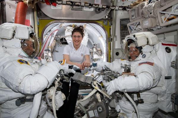 Astronautti Christina Koch (kuvassa keskellä) auttaa kollegojaan Nick Hagueta ja Anne McClainia avaruuspukuihinsa.