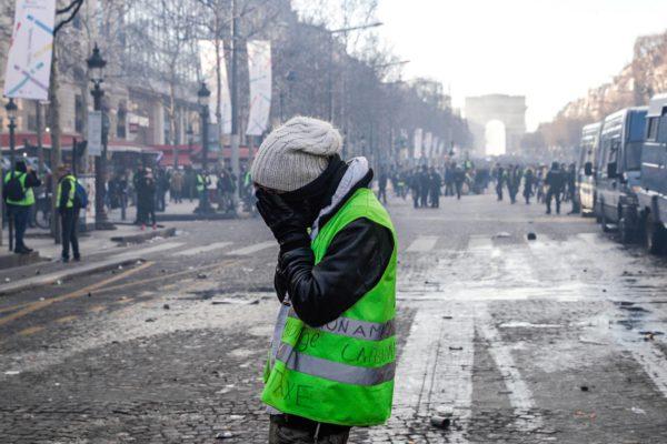 Champs-Elysées lauantaina 16. maaliskuuta. Naamioitunut aktivisti peittää kasvonsa mellakoiden keskellä.