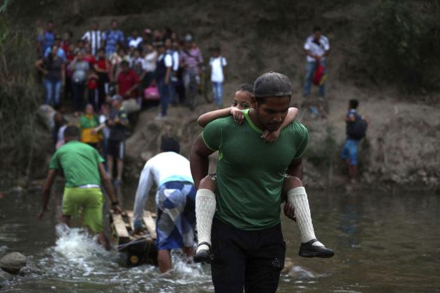Vapaaehtoistyöntekijä auttoi koululaistytön Tachirajoen yli Venezuelasta Kolumbiaan 6. maaliskuuta 2019.