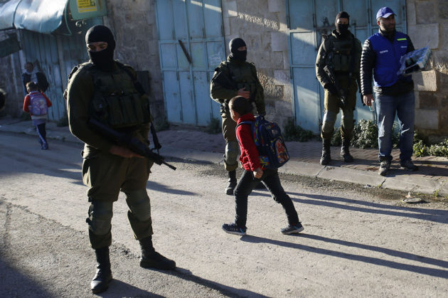 Lapsi ohitti israelilaisia sotilaita Hebronissa Länsirannalla 12. helmikuuta 2019.