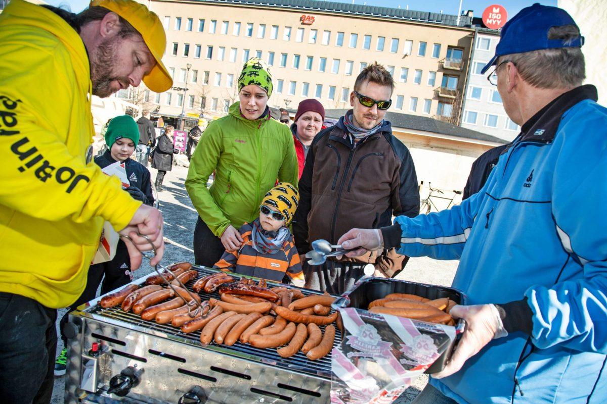 Joensuussa perussuomalaisten Sampsa Jääskeläinen (vas.) ja Eero Bogdanoff tarjoavat grillimakkaraa Katri Ojalalle ja Harri Karviselle.
