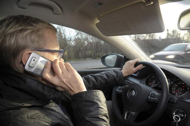 Naisautoilija puhuu kännykkään. Kuvituskuva.