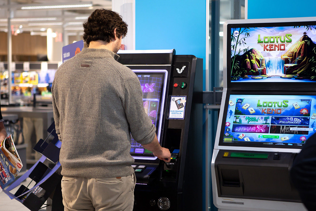 Mies pelaa rahapelikoneella kaupassa. Kuvituskuva. Veikkaus.