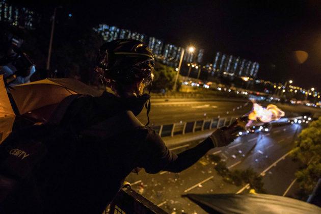 Mielenosoittaja heitti polttopullolla autoja, jotka yrittivät päästä mielenosoittajien rakentaman tiesulun läpi Hongkongin kiinalaiselle yliopistolle 15. marraskuuta 2019.
