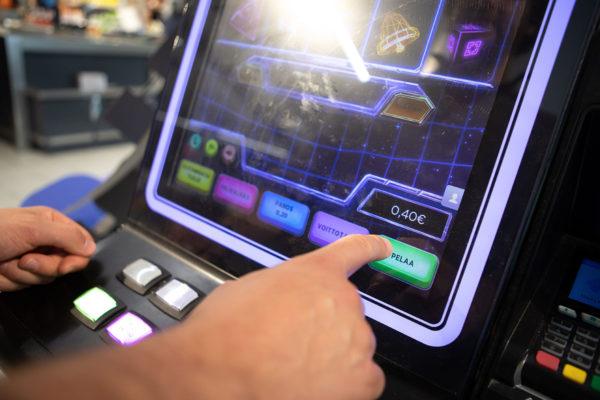 Mies pelaa rahapelikoneella kaupassa Helsingissä 16. elokuuta 2019.