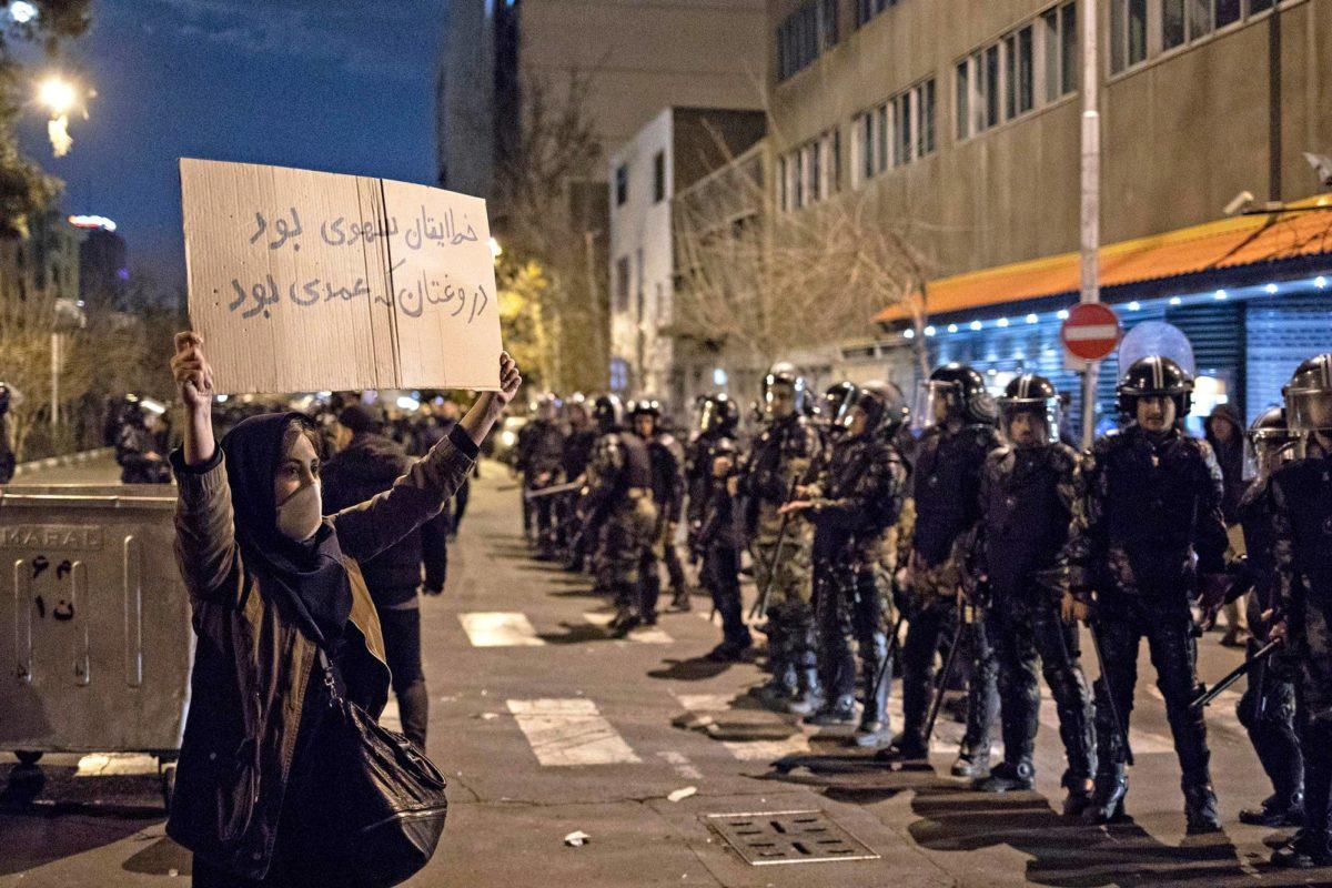"""Iranilaisnainen hallituksen vastaisessa mielenosoituksessa Teheranissa 11. tammikuuta. """"Virheenne oli tahaton, mutta valehtelunne tahallista"""", farsinkielisessä julisteessa lukee."""