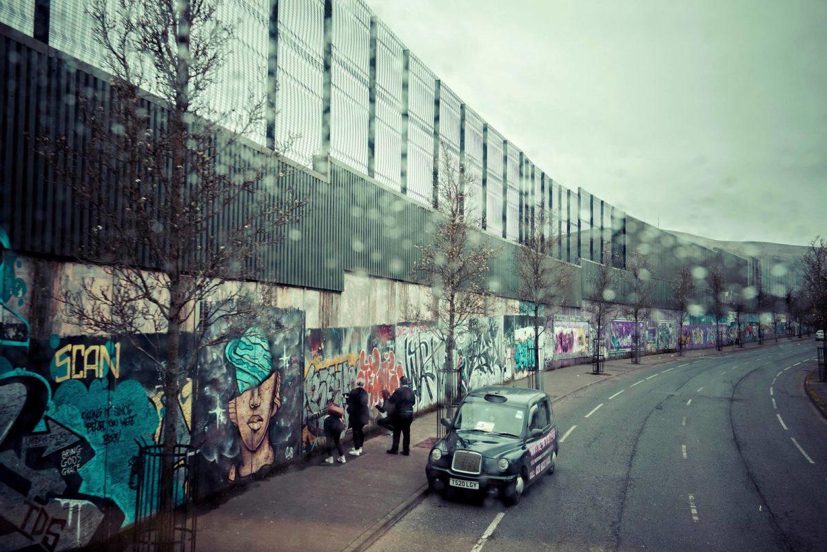 Katolisten ja protestanttien asuinalueita erottava muuri Belfastin Cupar Waylla. Muurin maalauksista on tullut turistinähtävyys.