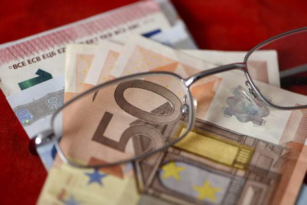 Rahaa ja silmälasit. Kuvituskuva.