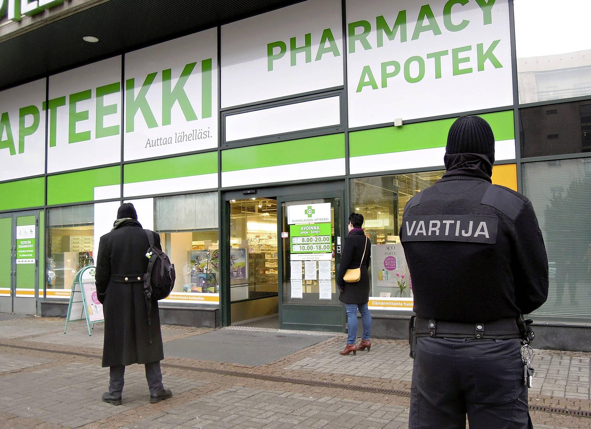 Vartija valvoi sisäänpääsyä Ruoholahden apteekin edustalla Helsingissä 17. maaliskuuta. Uusi asiakas pääsi sisään, kun yksi poistui. Terveydenhuollon tarvikkeiden ja lääkkeiden myyntiä voidaan rajoittaa.