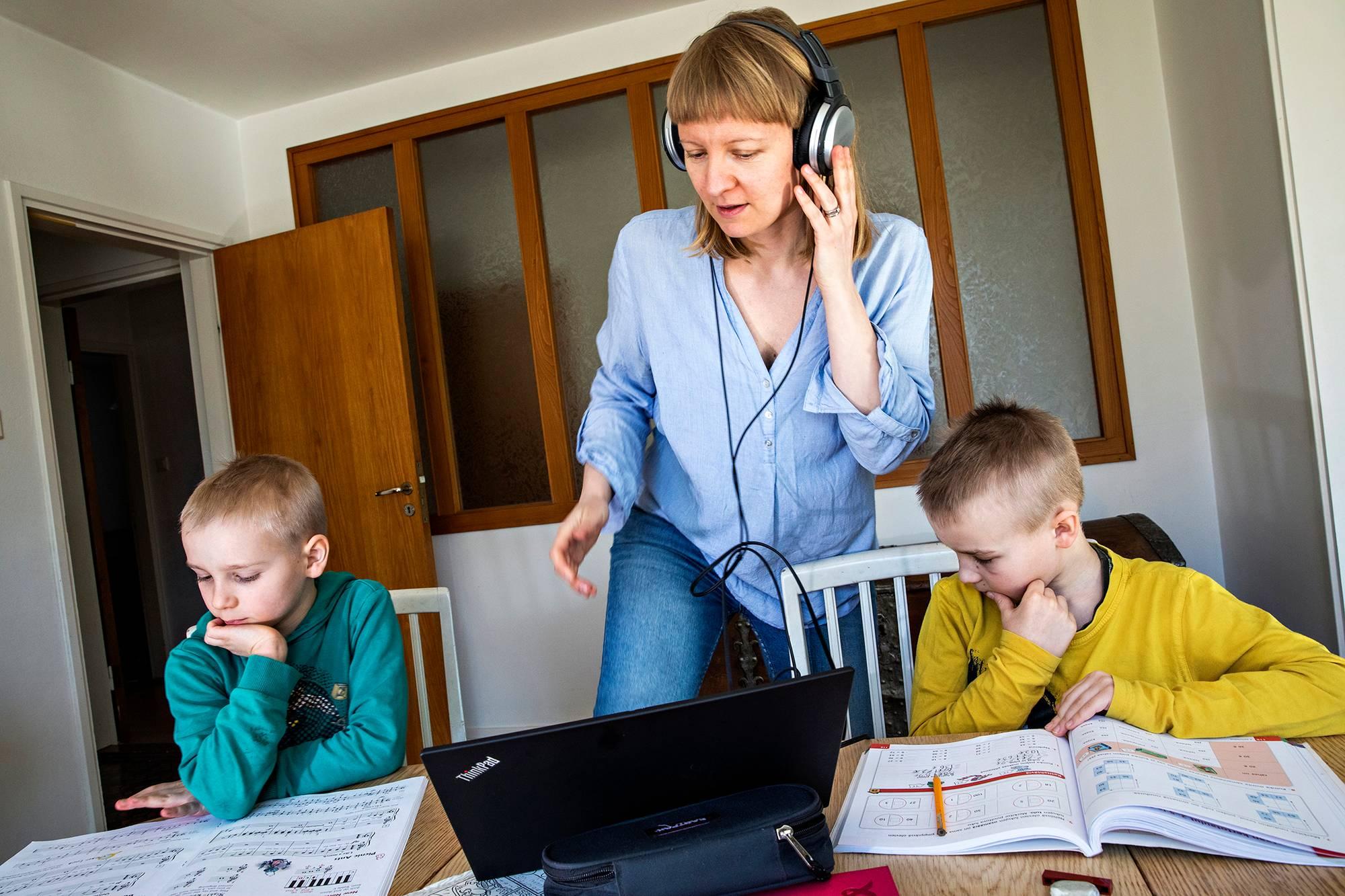 """Hyvinkääläinen viestintäasiantuntija Anna Salminen pakeni perheineen Hankoon. Loma-asunnolla äiti ja ykkös- ja kolmosluokkalaiset pojat totuttelevat etätöihin. Virtuaalipalavereissa istumisen lomassa äiti opastaa poikia koulutehtävissä. """"Lapset ovat onnellisia, kun saadaan olla yhdessä"""", Salminen sanoo. <span class=""""typography__copyright"""">©&nbsp;Markus Jokela</span>"""