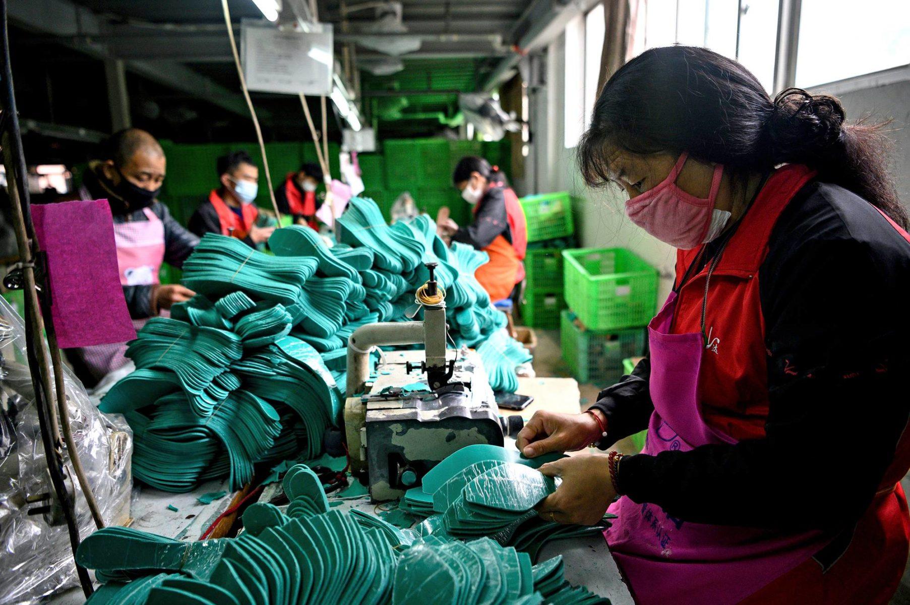 Kenkätehtaan työntekijät suojautuivat koronavirukselta helmikuussa Kiinan Wenzhoussa.