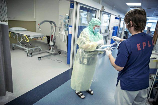 Suoja-asuun pukeutunut hoitaja ja avustava hoitaja koronapotilaiden osastolla Turun yliopistollisessa keskussairaalassa 3. huhtikuuta 2020.
