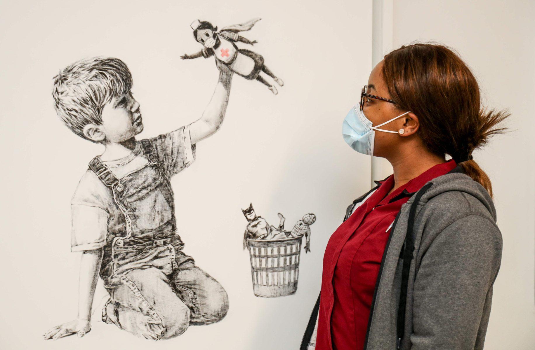 Työntekijä katsoo Banksyn Game Changer -taideteosta Southamptonin sairaalassa Britanniassa.