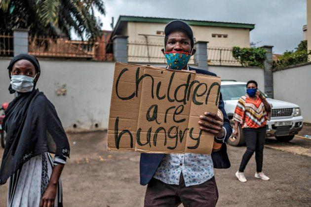 """""""Lapset ovat nälkäisiä"""", julisti mielenosoittajan kyltti Ugandan pääkaupungissa Kampalassa 18. toukokuuta."""