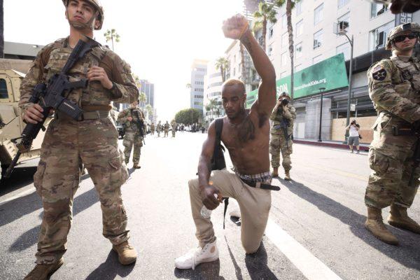Mielenosoittaja polvistui George Floydin kuolemaa muistaneella marssilla Los Angelesissa 2. kesäkuuta.