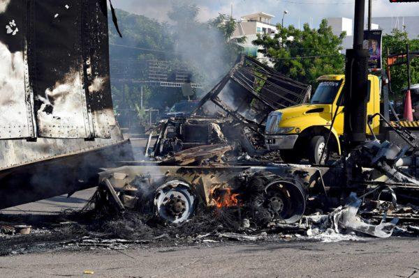 Culiacánin tulitaistelun jälkiä. Kartellin asemiehet polttivat rekkoja ulosmenoteille estääkseen vangitun huumepomon siirtämisen lentokentälle.