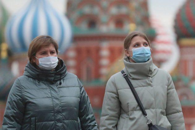 Kasvomaskeihin pukeutuneet naiset kävelivät Moskovan Punaisella torilla 26. lokakuuta.