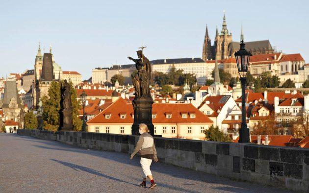 Kasvomaskia käyttävä nainen ylitti historiallista Kaarlensiltaa Tšekin pääkaupungissa Prahassa 18. syyskuuta.
