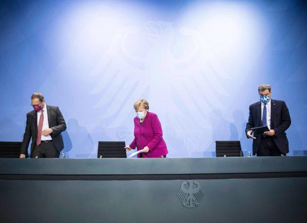 Liittokansleri Angela Merkel koronatiedotustilaisuudessa Berliinin pormestarin Michael Müllerin (vas.) ja Baijerin pääministerin Markus Söderin kanssa.