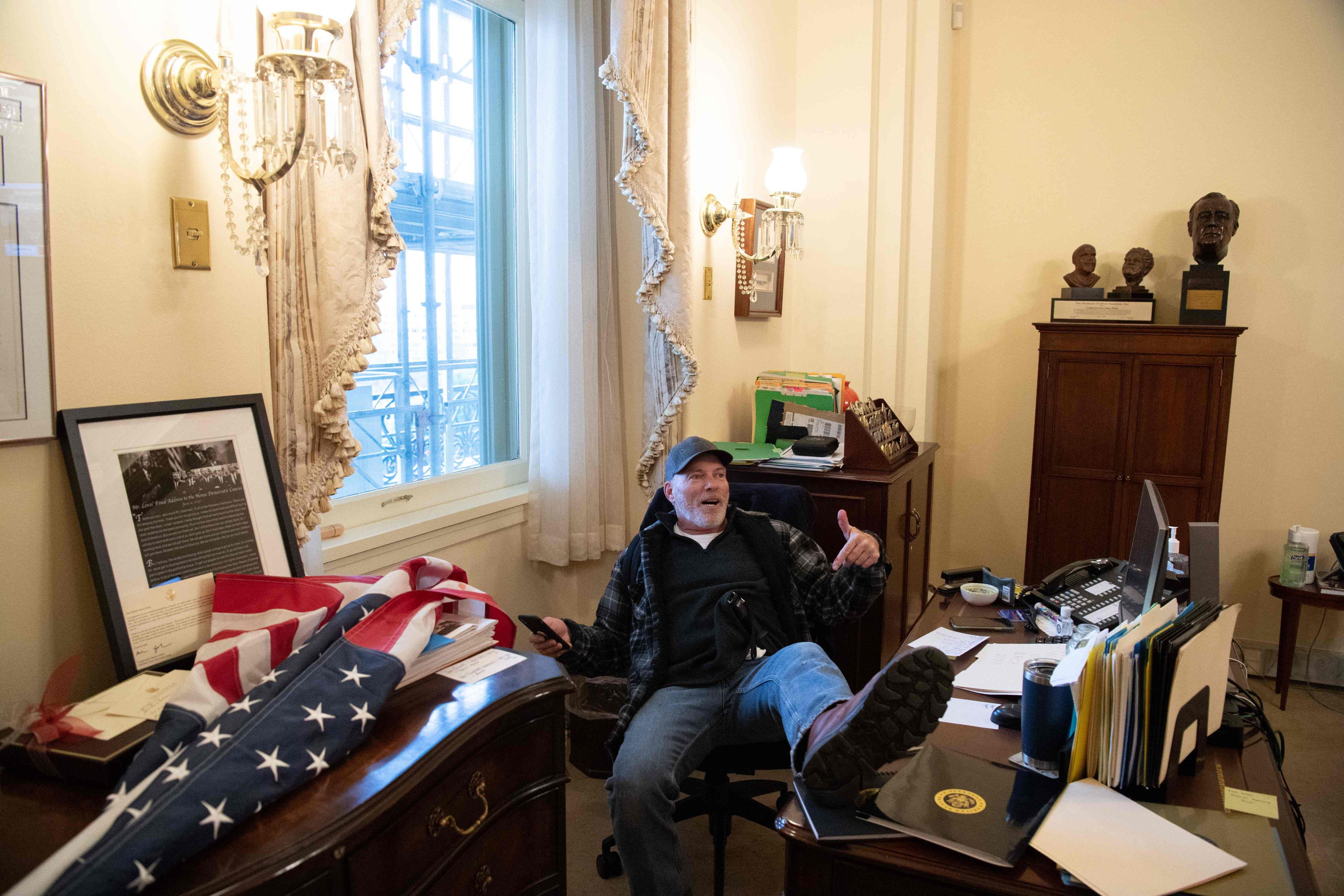 Yksi hyökkääjistä edustajainhuoneen puhemiehen Nancy Pelosin työhuoneessa.