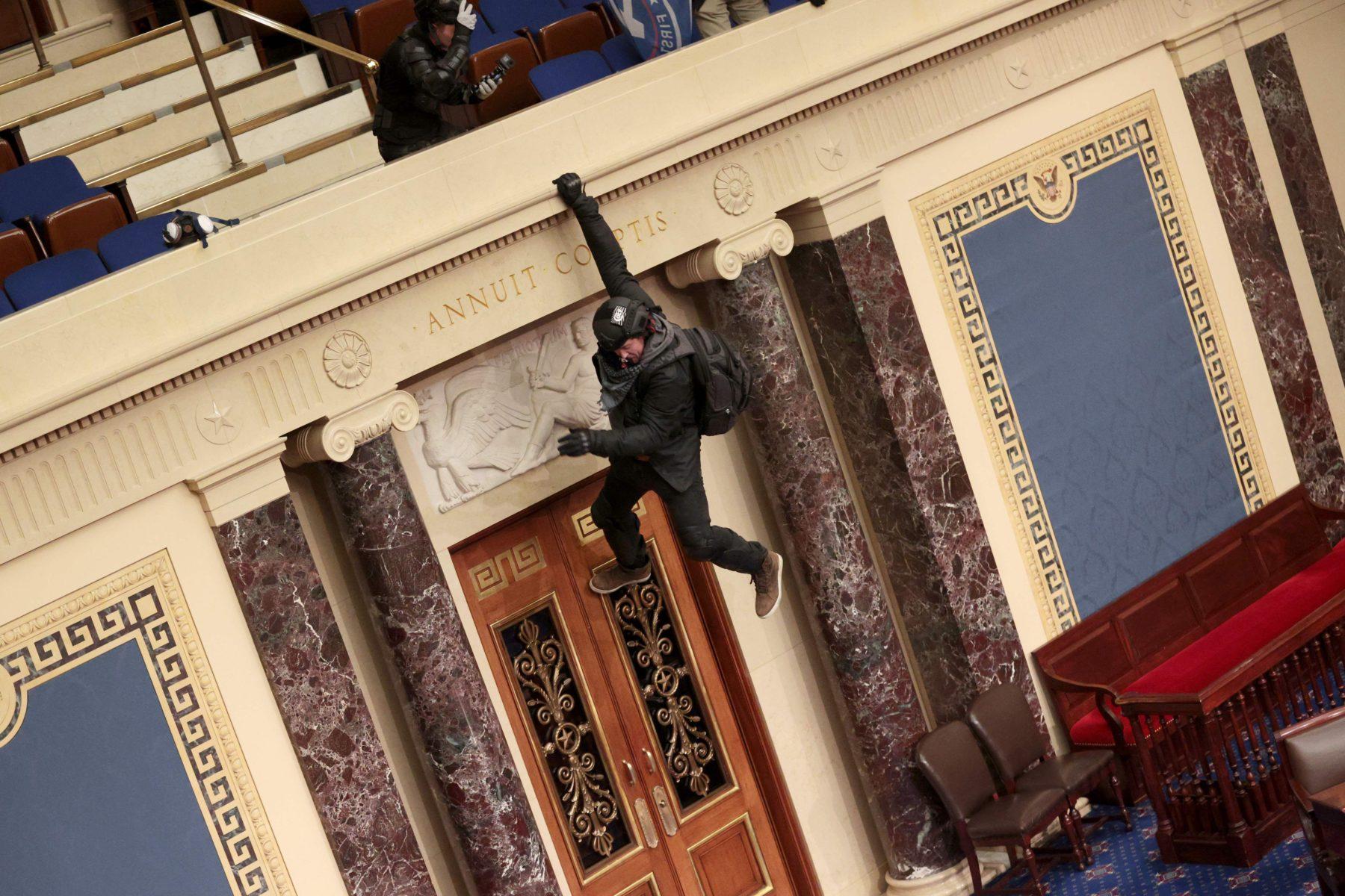 """Tunkeutuja roikkuu senaatin parvekkeelta. Hänen takanaan on Yhdysvaltain valitollisiin tunnuksiin kuuluva lause<i>""""Annuit Cœptis"""", Jumala</i>puoltaa tehtäväämme."""