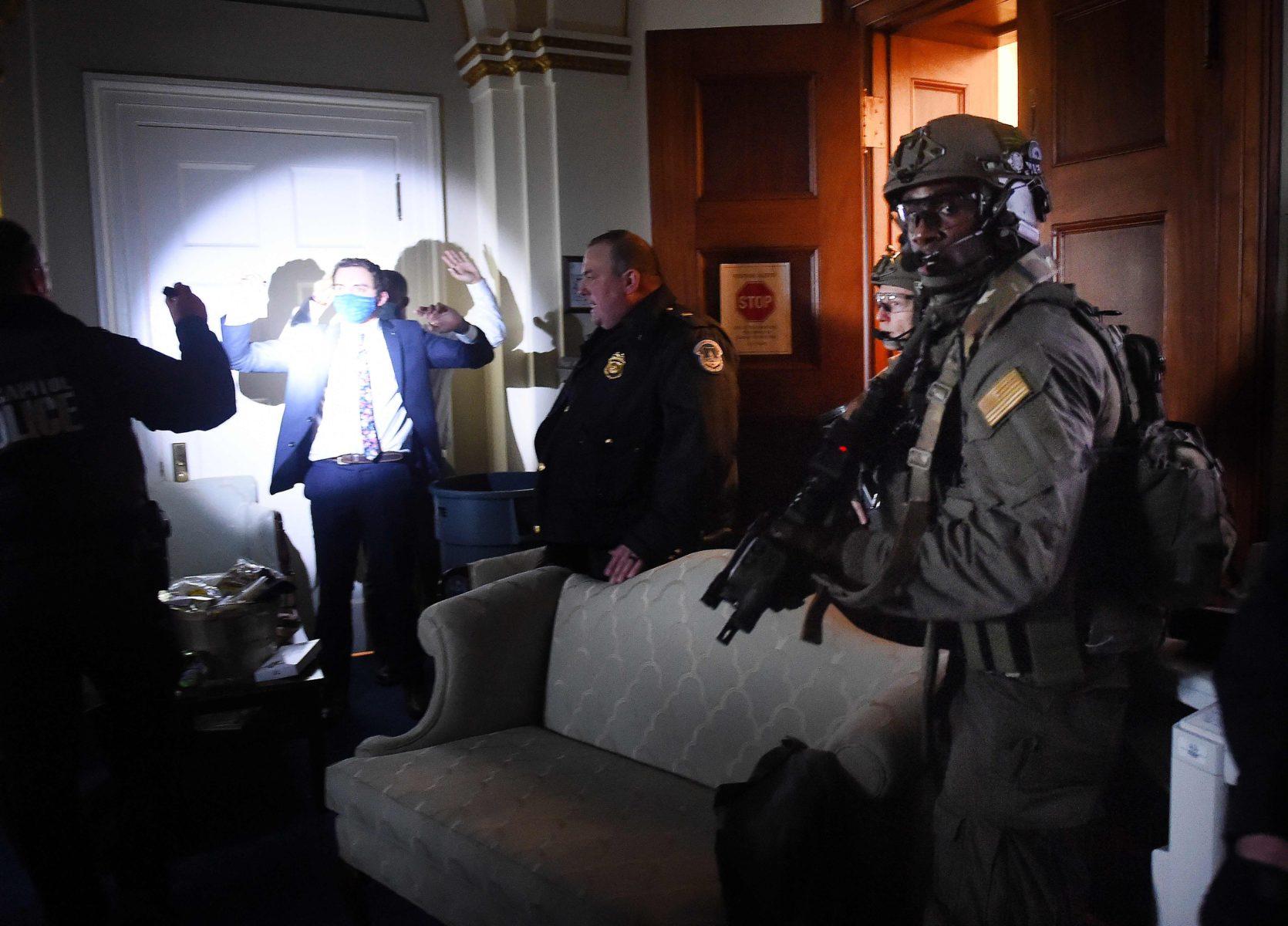 Yöllä poliisit ottivat rakennuksen haltuunsa. Kongressin työntekijä odotti kädet ylhäällä, kun Capitolin poliisin iskujoukko tarkisti huoneessa olevat.