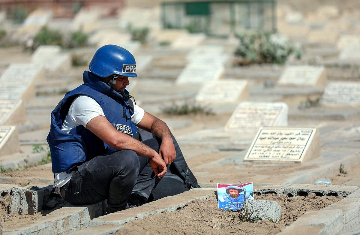Kollega suri pommi-iskussa Jemenissä kuollutta toimittaja Adib al-Janania tämän haudalla 2. tammikuuta 2021.
