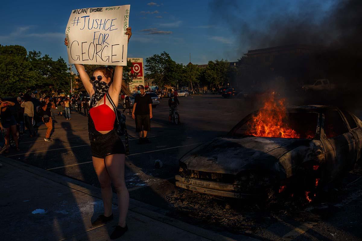 """Mielenosoittaja pitelee palavan auton edessä kylttiä, jossa lukee """"Justice for George"""" Minneapolisissa 29. toukokuuta 2020. George Floydin kuolema 25. toukokuuta käynnisti protestit, jotka jatkuivat ympäri maailmaa Black Lives Matter -mielenosoituksina."""