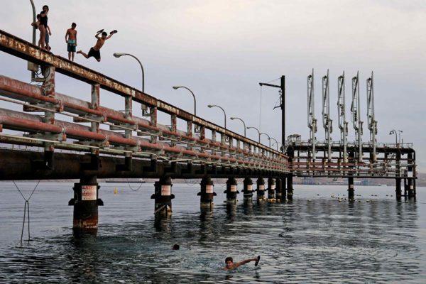 Nuoret hyppivät hylätyltä öljylaiturilta Punaiseenmereen Israelin Eilatissa helmikuussa 2021. Ympäristöjärjestöjen mukaan öljyä putkeen kuljettavat tankkerit uhkaavat ainutlaatuisia koralliriuttoja.