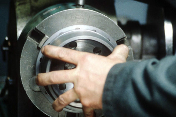 Metalliteollisuuden työntekijän kädet sorvilla.