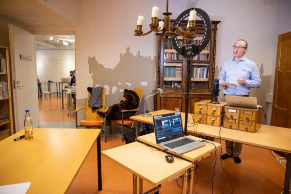 Harri Ahonen luennoi Pornaisten kirjaston kellarissa Pohjois-Norjan rannikkoreiteistä. Hän puhuu kameralle, yleisö seuraa suoraa lähetystä Youtubessa.