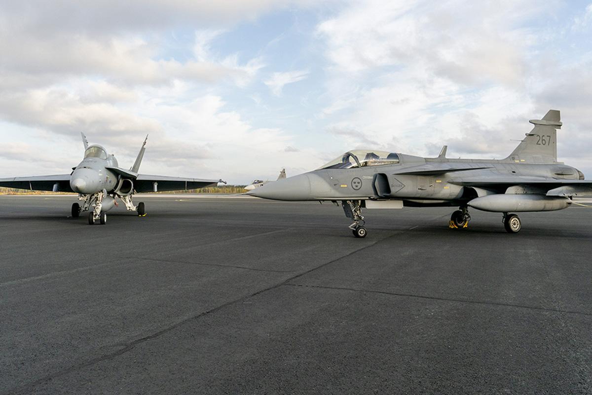 Vasemmalla Suomen Hornet hävittäjä ja oikealla Ruotsin Jas Gripen -hävittäjä Rovaniemen tukikohdan kentällä lokakuussa 2020 Ruska 20 -harjoituksessa.