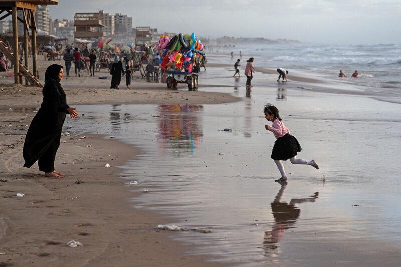 Palestiinalainen äiti leikki tyttärensä kanssa Gazan rannalla 22. toukokuuta 2021 tulitauon alettua.