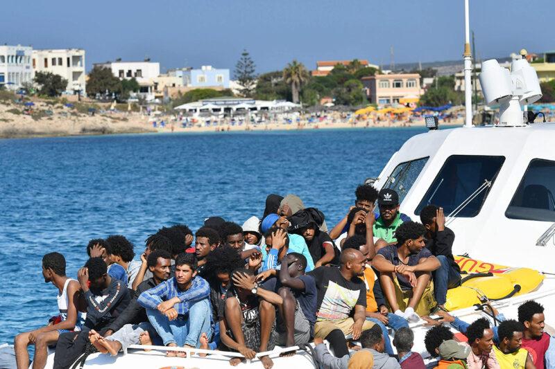 Libyasta ja Tunisiasta Välimeren yli saapuneita siirtolaisia Italian rannikkovartioston veneellä Lampedusan saarella elokuussa 2020.