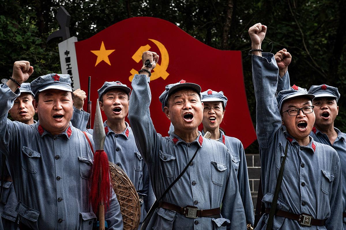 Turistit poseerasivat Kiinan armeijan vanhoissa univormuissa Pitkä marssi -teemapuistossa Kiinan Hubein provinssissa 26. kesäkuuta.