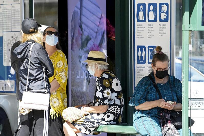 Maskin käyttö joukkoliikenteessä voi jatkua vielä pitkään. Kasvomaskia käyttäviä matkustajia raitiovaunupysäkillä Helsingin keskustassa 1. heinäkuuta 2021.